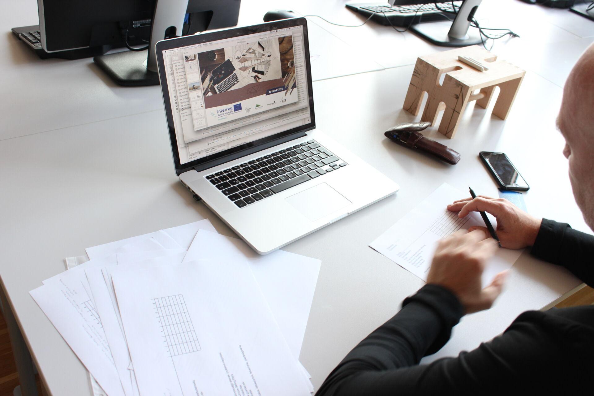 Mensch sitzt vor Laptop mit Ausschreibung zu einem Wettbewerb